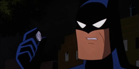 A screenshot from Batman the Animated Series. Batman wears his cowl and peers closely at a coin held between his fingers.