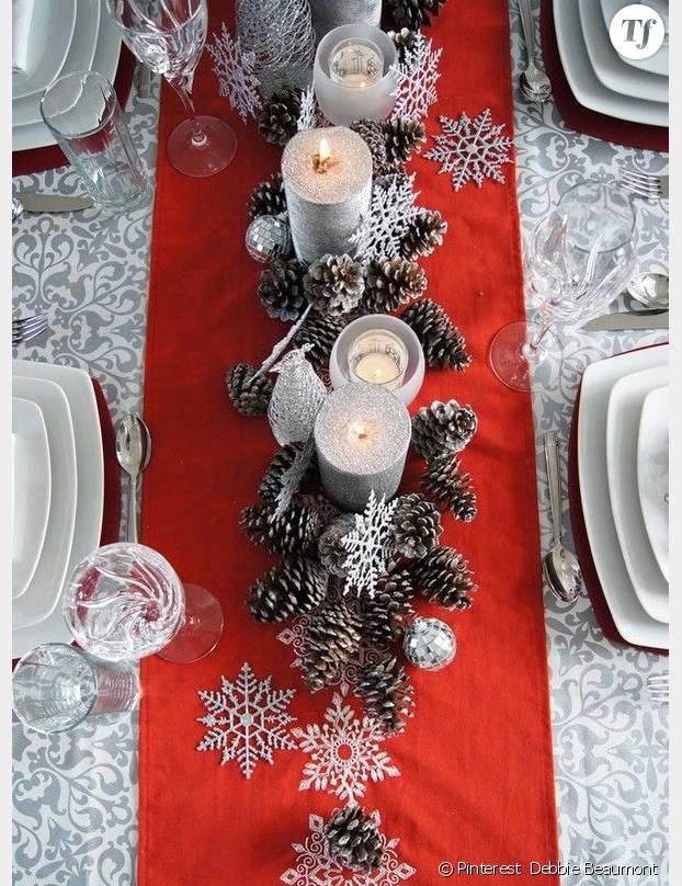 on aime le centre de table rouge avec ses pommes de pin argents qui donne un with idee deco table noel rouge et blanc