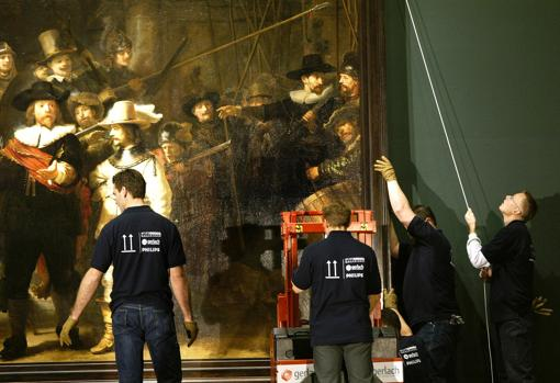 Dutch museum workers, taking down the painting in 2003, which was last moved during the restoration works of the Rijksmuseum