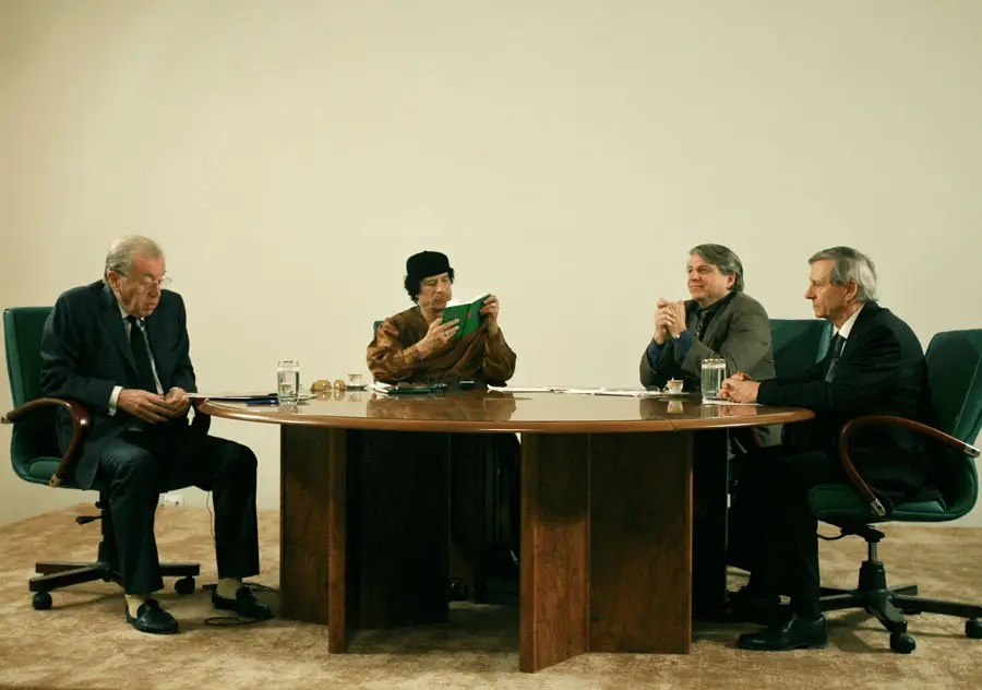 "Qaddafi holds a copy of the Green Book during a debate that was moderated by David Frost, (left) for the BBC. The program also hosted American political theorist Benjamin Barber (second right) and British social scientist Anthony Giddens, (right), on the sidelines of celebrations marking the 30-year anniversary of the declaration of the ""rule of the masses, in Libya, March 2, 2007"