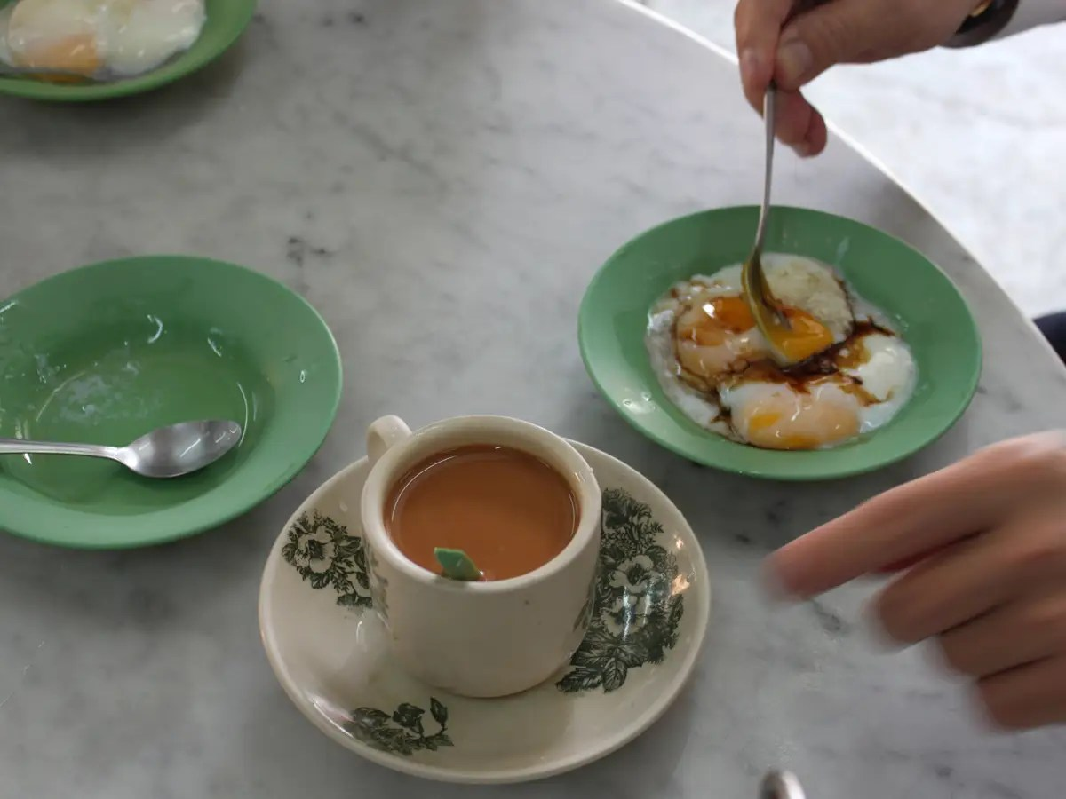 The kaya toast is served with coffee and soft-boiled eggs. You're supposed to add soy sauce and pepper to the eggs, then dip the kaya toast into the warm, liquidy concoction.
