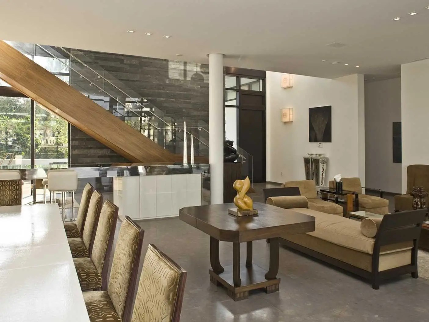 Inside, the living, dining and kitchen areas are combined in one large space with gray limestone flooring and stark white walls. The home has six bedrooms and nine bathrooms.