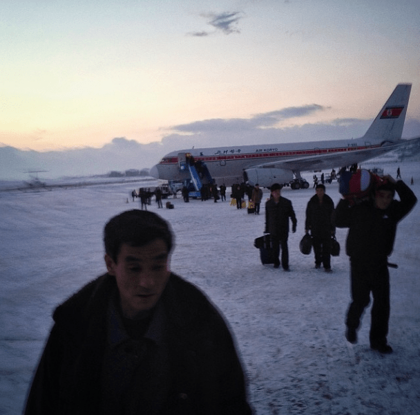 'Passengers walk across the snowy tarmac at Pyongyang's airport as an Air Koryo flight arrives from Beijing tonight'