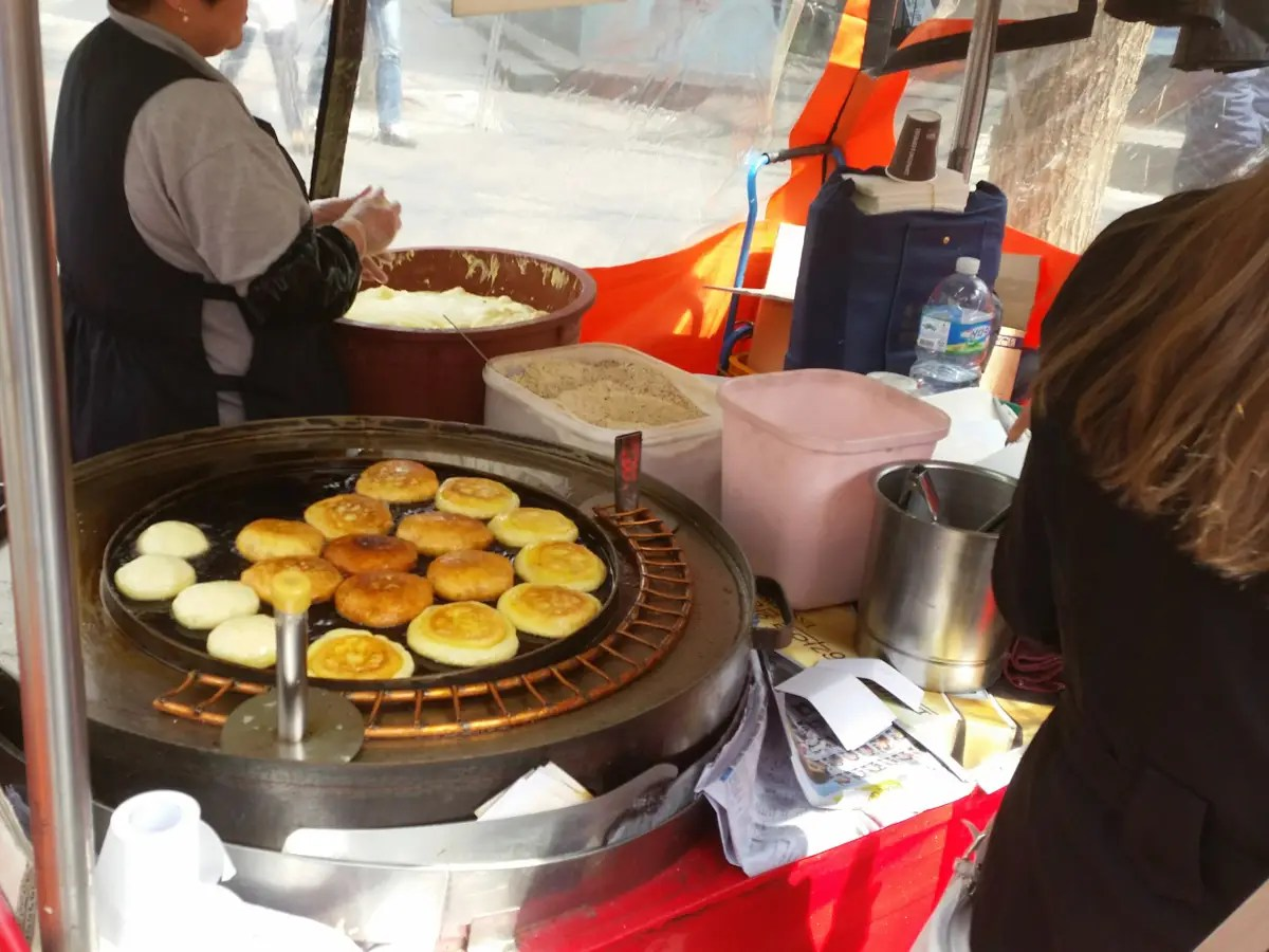 This stand had sweet cakes frying on a big pan.