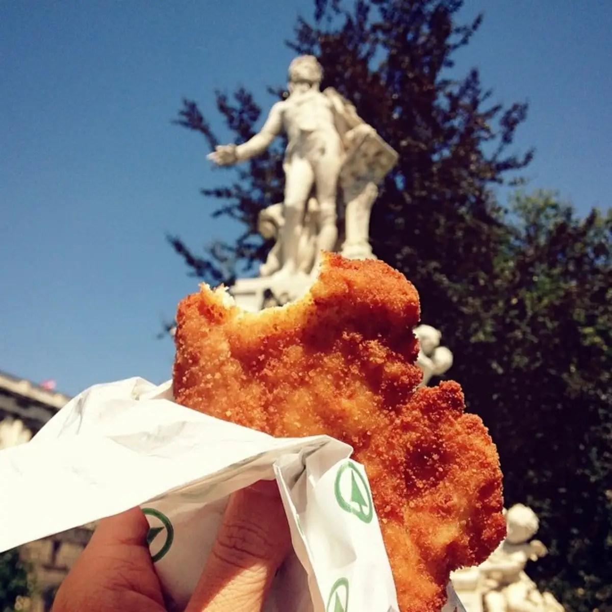 Schnitzel in front of the Mozart statue in Vienna.