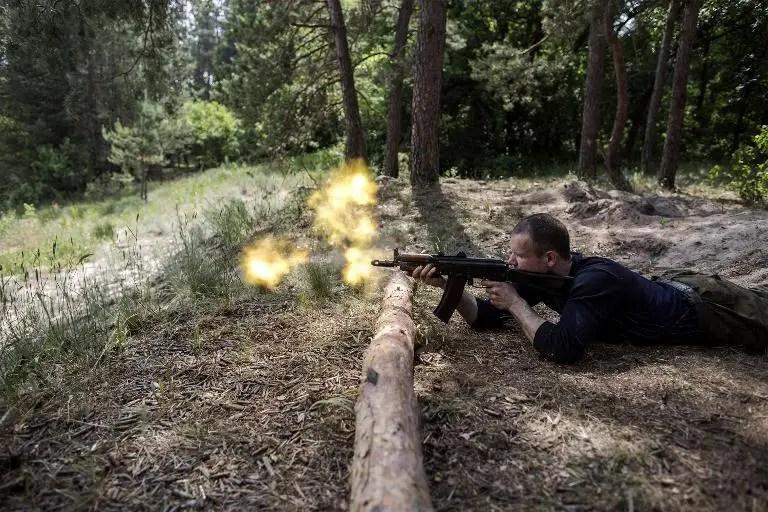 A Ukrainian pro-regime fighter fires his assault rifle during training exercises near Pokrovskoe, eastern Ukraine, on June 4, 2015