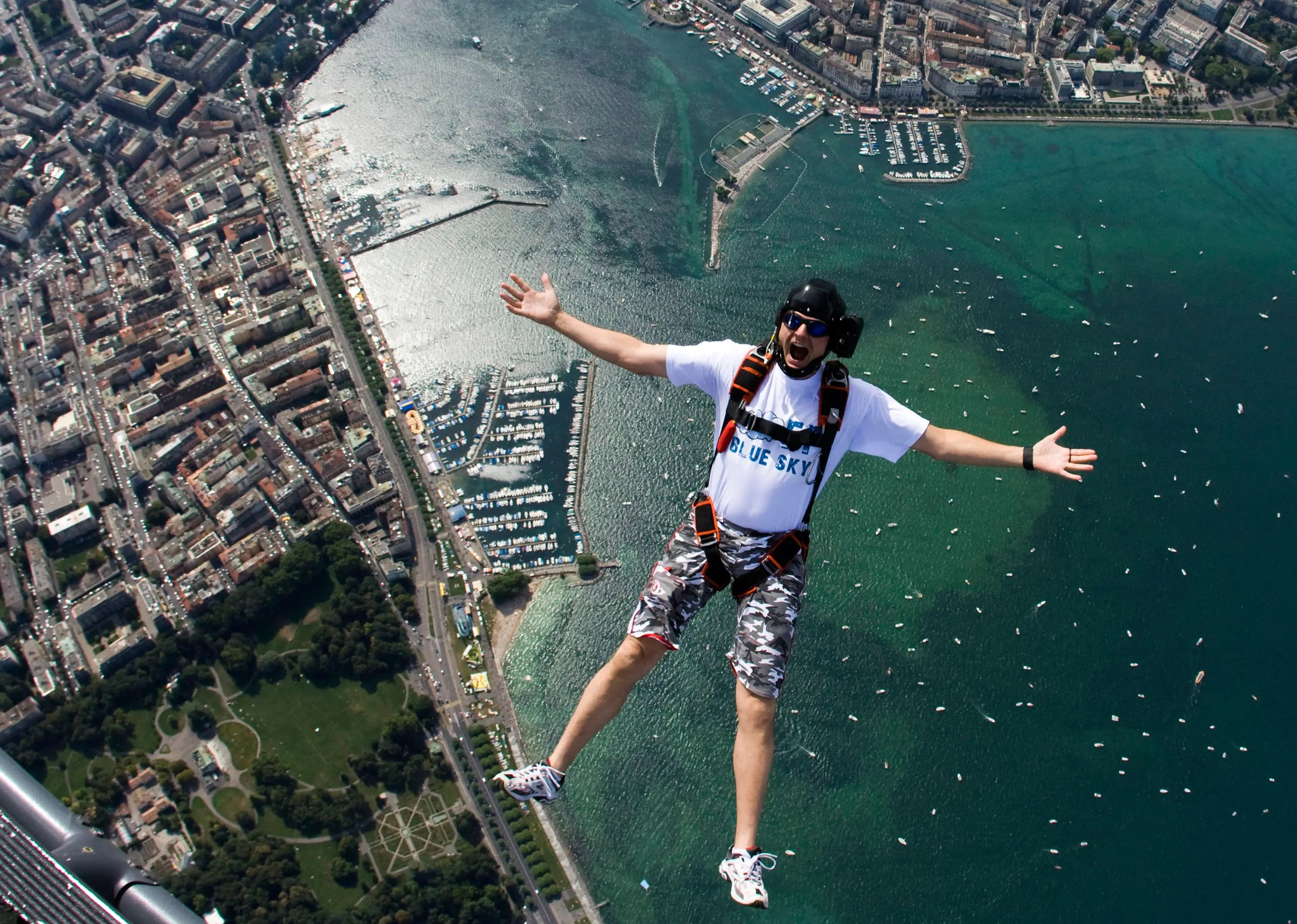 Christoffe Jonin of the FF Blue Sky Team jumps out of a helicopter with a parachute, 1,300 meters above Lake Leman (Lake Geneva) and the city of Geneva, during the final day of Fetes de Geneve.