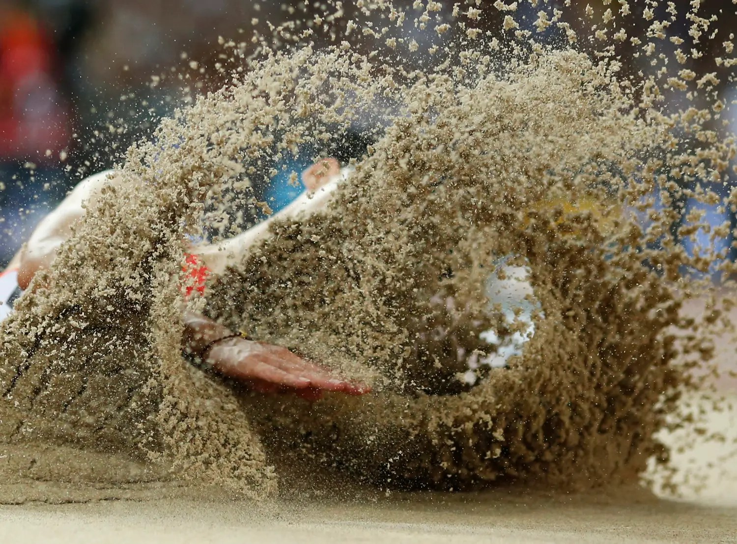 China's Wang Jianan emerges from the sand after a long jump.