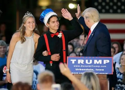 Republican presidential candidate, businessman Donald Trump high-fives homecoming king Austin Cook as queen Eylse Pescott, left, looks on during a rally at Urbandale High School, Saturday, Sept. 19, 2015, in Urbandale, Iowa. (AP Photo/Charlie Neibergall)