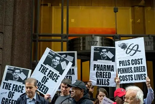 FILE - In this Thursday, Oct. 1, 2015, file photo, activists hold signs containing the image of Turing Pharmaceuticals CEO Martin Shkreli in front the building that houses Turing's offices, in New York, during a protest highlighting pharmaceutical drug pricing. After weeks of criticism from patients, doctors and even other drugmakers for hiking a life-saving medicine's price more than fiftyfold, Turing Pharmaceuticals is reneging on its pledge to cut the 0-per-pill price. But a competitor's 99-cent capsule version is selling well. (AP Photo/Craig Ruttle, File)