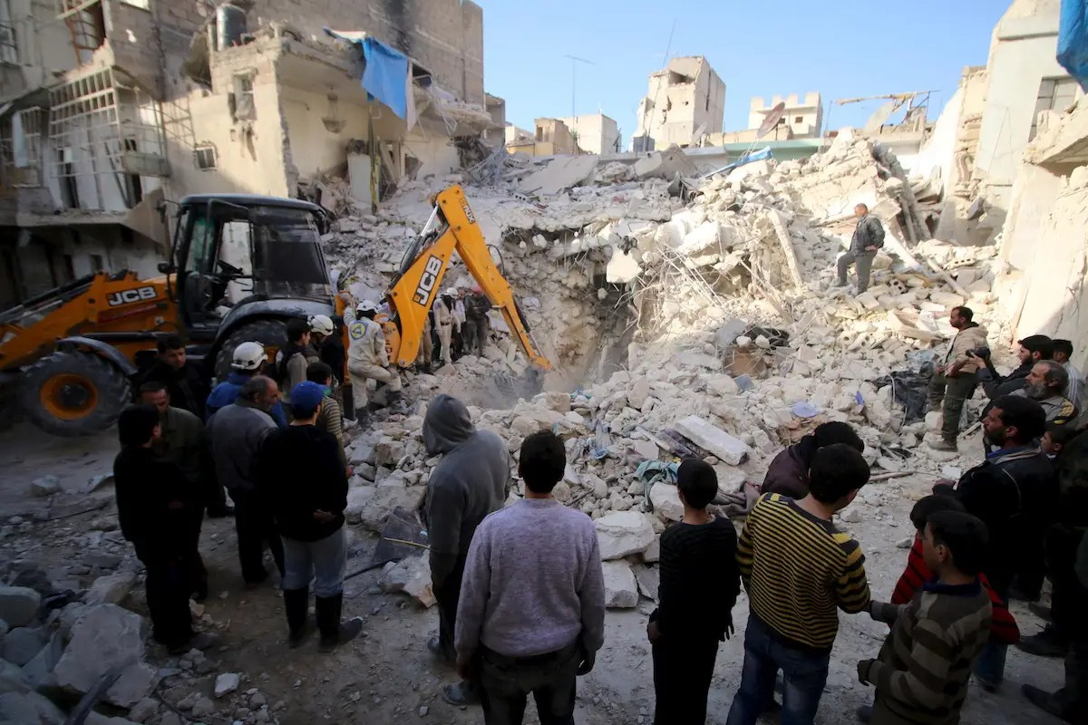 Civil defence members search for survivors after airstrikes by pro-Syrian government forces in the rebel held al-Qaterji neighbourhood of Aleppo, Syria February 14, 2016. REUTERS/Abdalrhman Ismail
