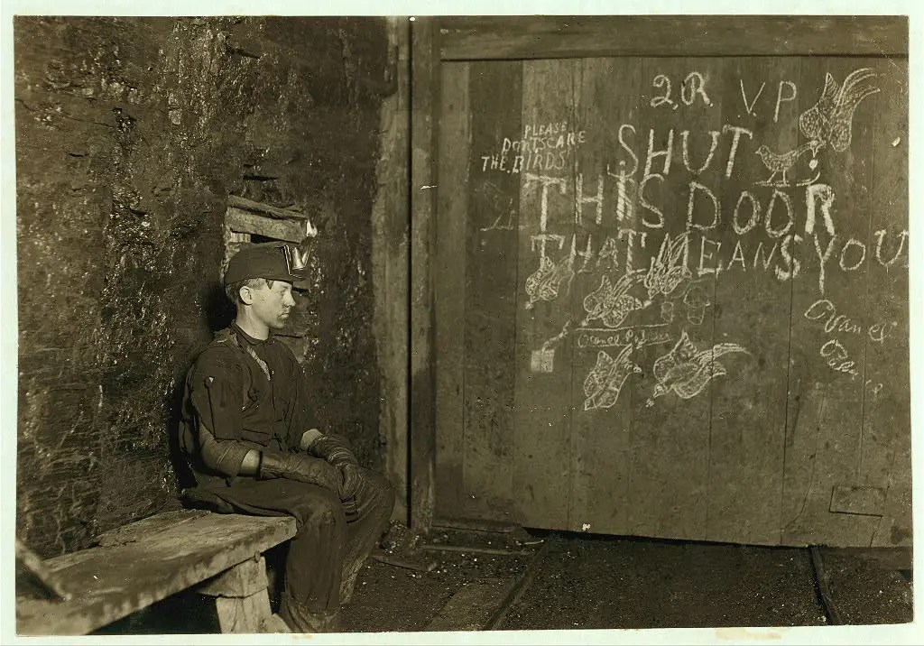 Vance, a trapper Boy, 15 years old. He had trapped for several years in a West Virginia coal mine for $0.75 a day for 10 hours work. All he does is open and shut this door: Most of the time he sits here idle, waiting for the cars to come. On account of the intense darkness in the mine, the hieroglyphics on the door were not visible until plate was developed. Taken in September 1908.