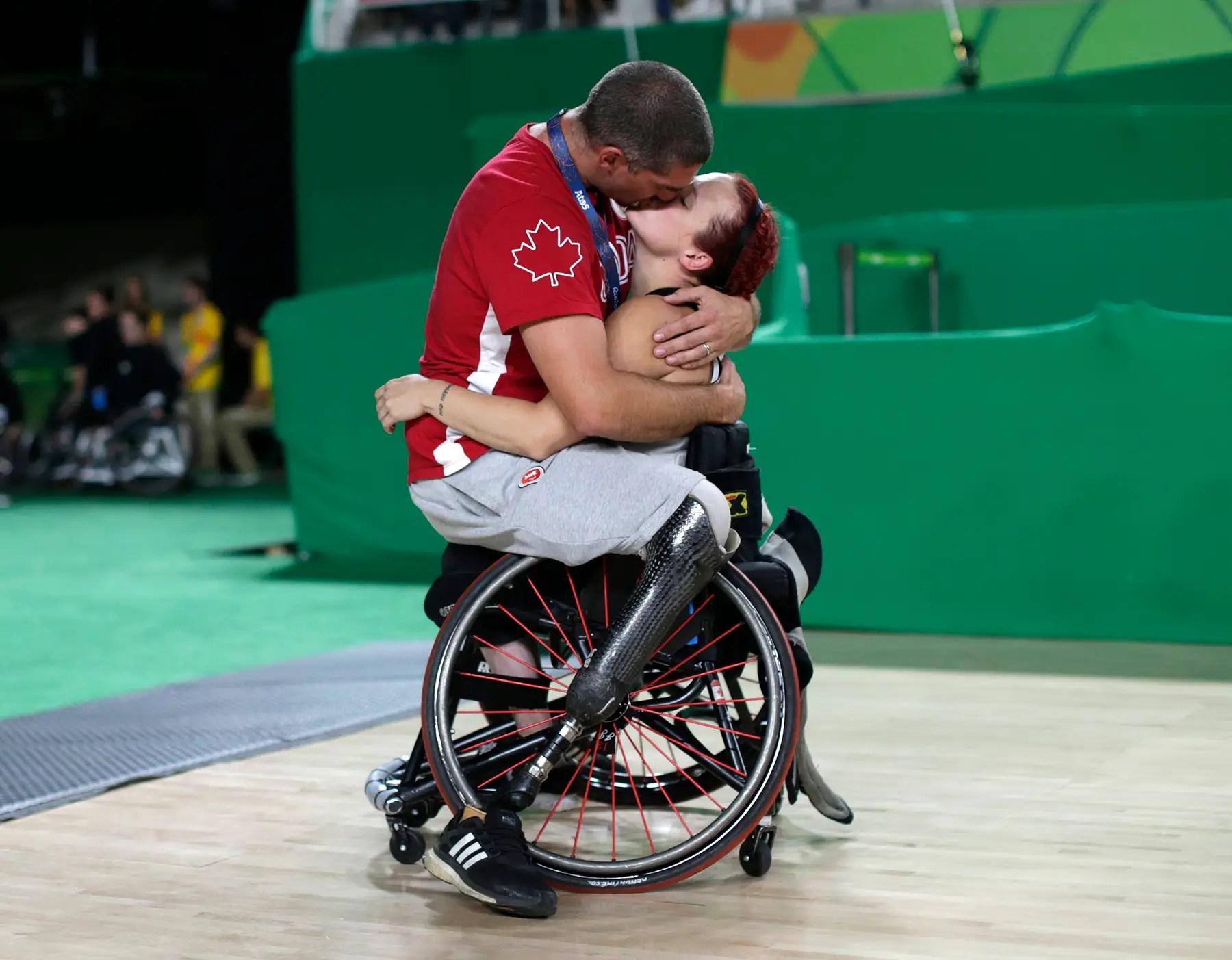 El jugador de baloncesto en silla de ruedas equipo masculino Adam Lancia de Canadá besa a su esposa Jamey Jewells que juega para el equipo femenino.