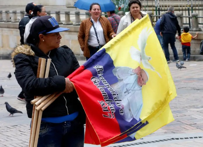 A woman sells flags with the image of Pope Francis outside the Cathedral of Bogota in Bolivar Square, Colombia September 2, 2017. REUTERS/Henry Romero