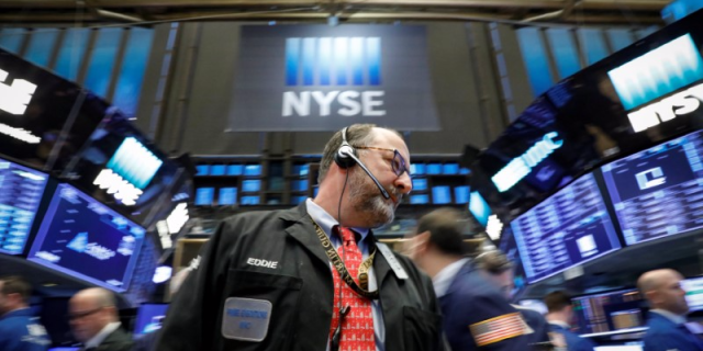 FILE PHOTO - Traders work on the floor of the New York Stock Exchange, (NYSE) in New York, U.S., February 26, 2018. REUTERS/Brendan McDermid