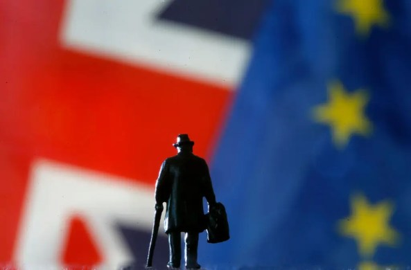 A small toy figure is seen in front of British and European flags