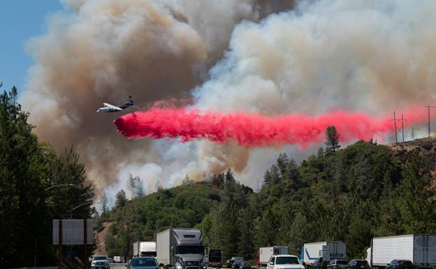 A plane tries to put out a fire along a busy highway in California, near the town of Shasta Lake.