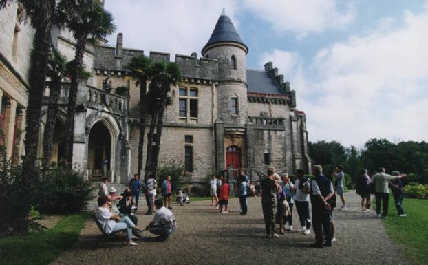 Un groupe de touristes est concentré aux portes du château.