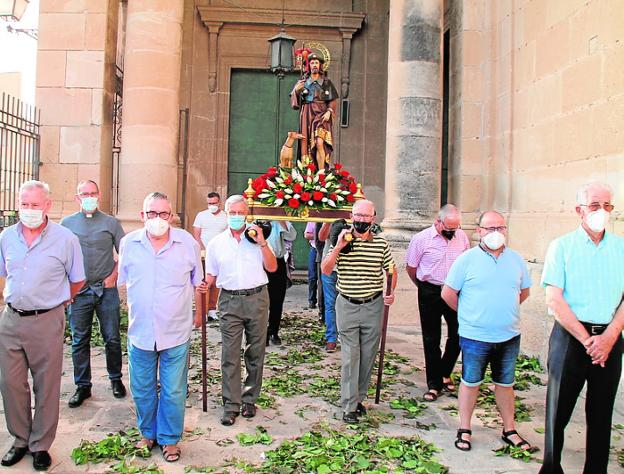 Neighbors carry San Roque, at the doors of the church, yesterday.