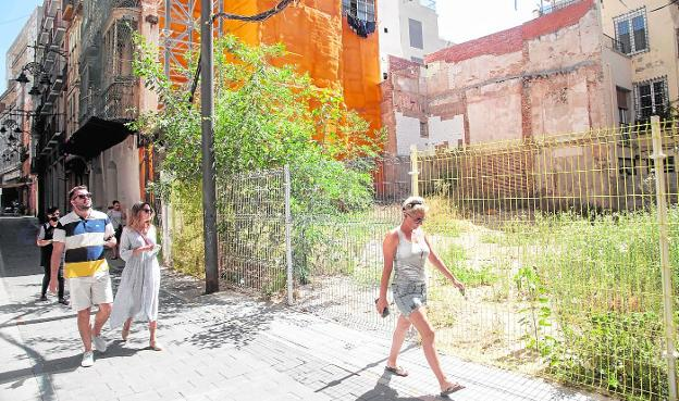 Several people walk along Cuatro Santos Street, in front of a lot owned by a bank and full of weeds.