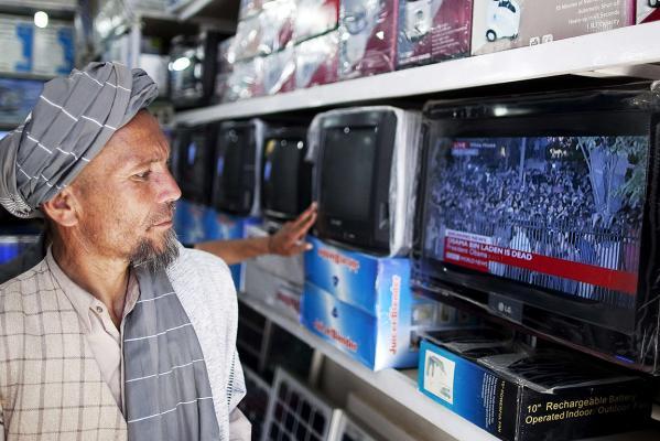 A man walks past a television reporting the death of al Qaeda leader Osama bin Laden in Kabul.