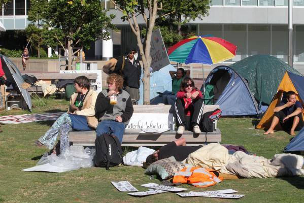 Photo of protesters sitting on park benches, surrounded by tents and signs at the Occupy Auckland protest
