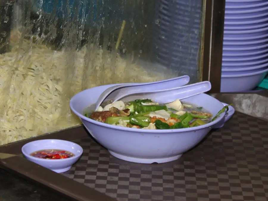 Fish ball soup is served piping hot with a side of chilis for an extra kick.
