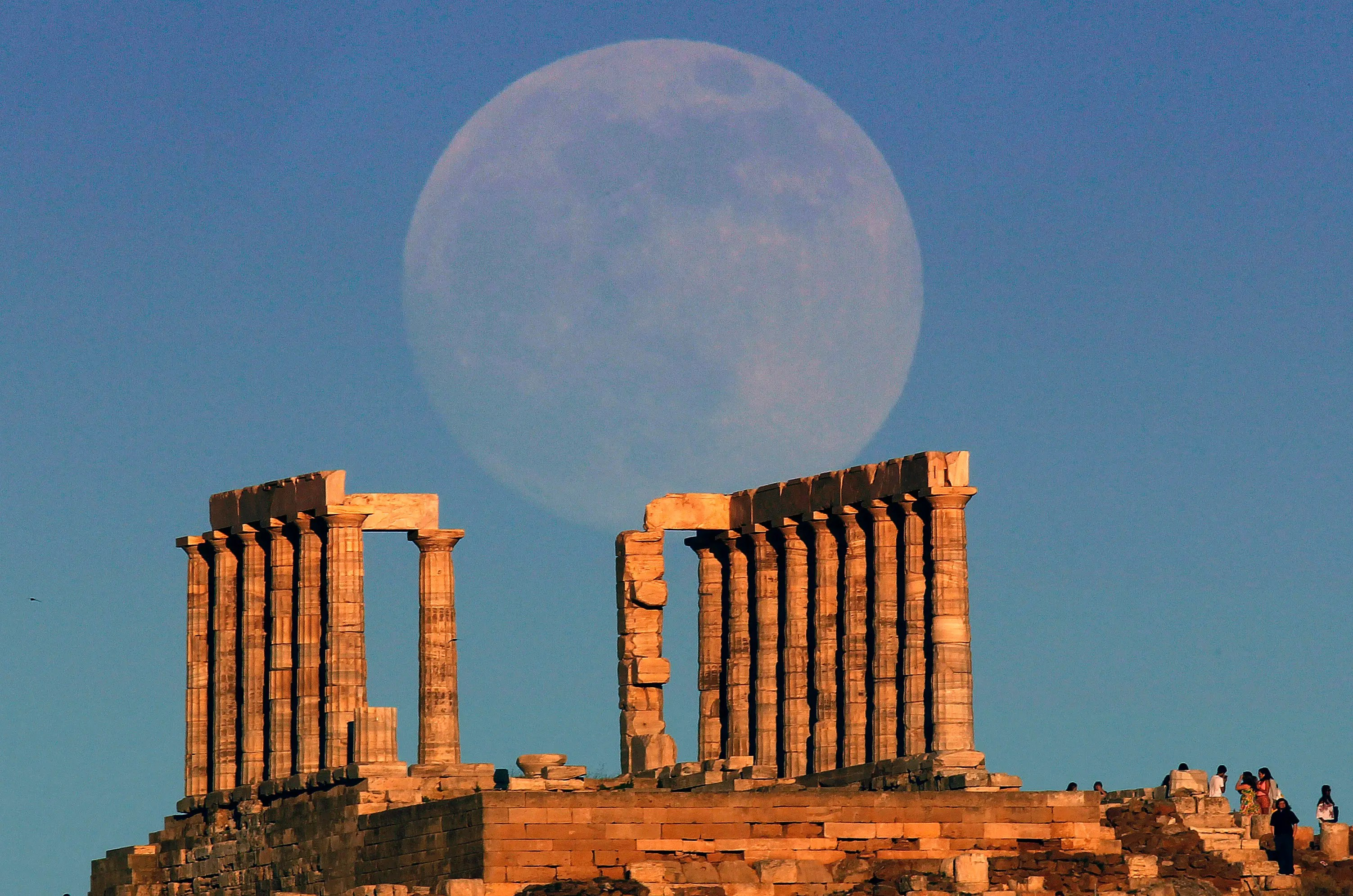 The supermoon rises over the temple of Poseidon, the ancient Greek god of the seas, in Cape Sounion, Greece.