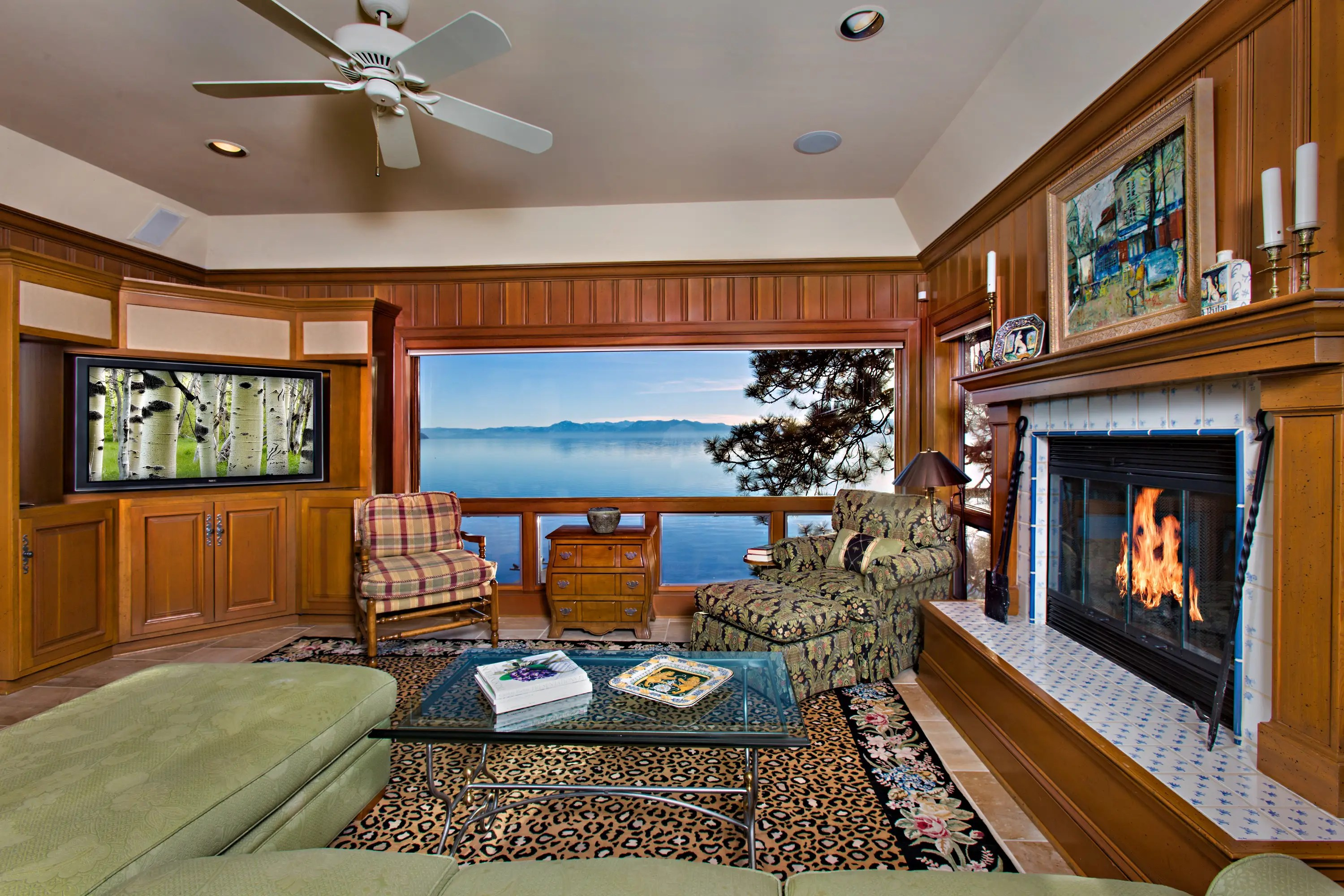 The living room includes wood-paneled walls and an oversized fireplace.