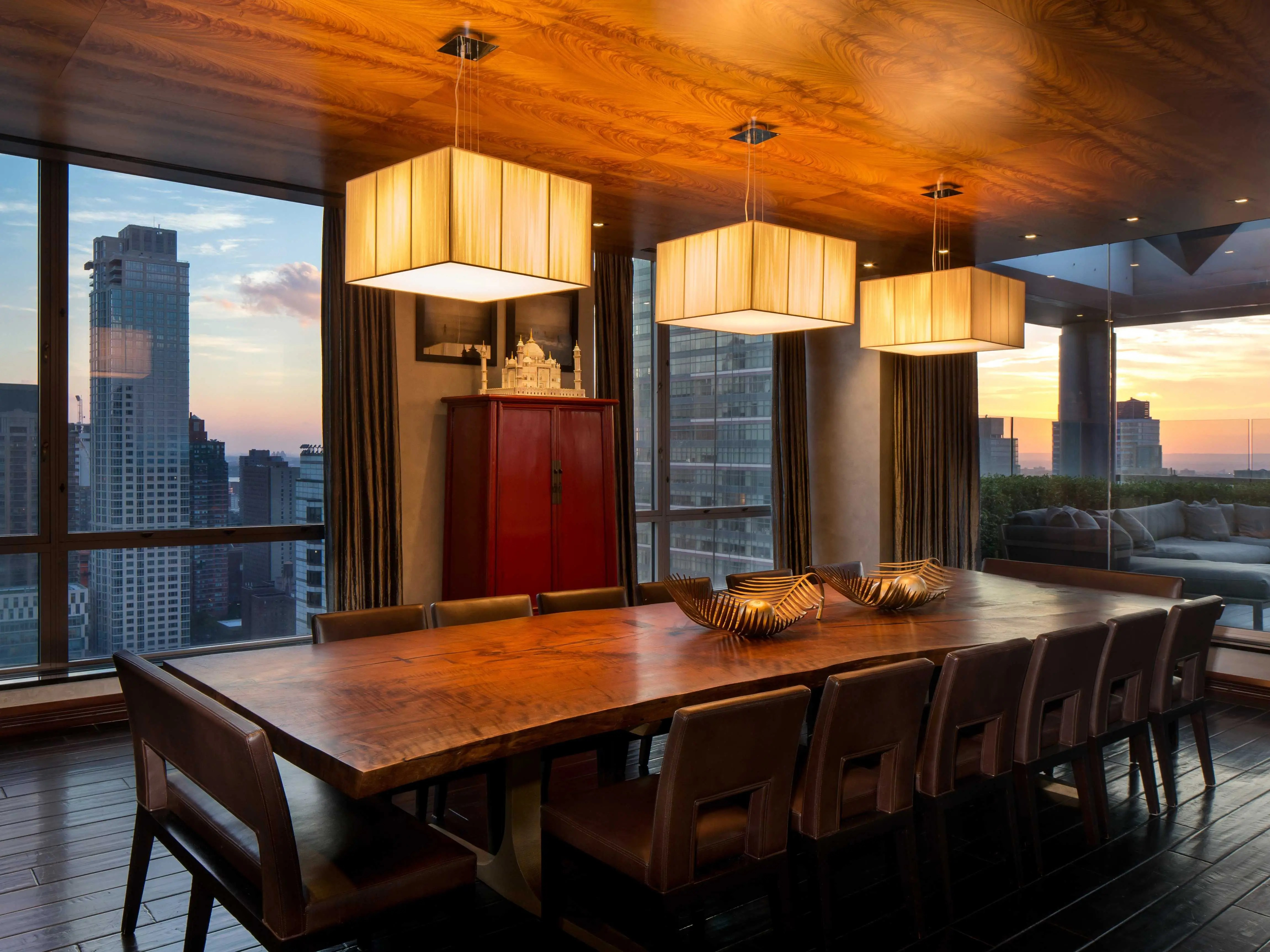 The dining room has a paneled, exotic wood ceiling and a massive table for entertaining guests.