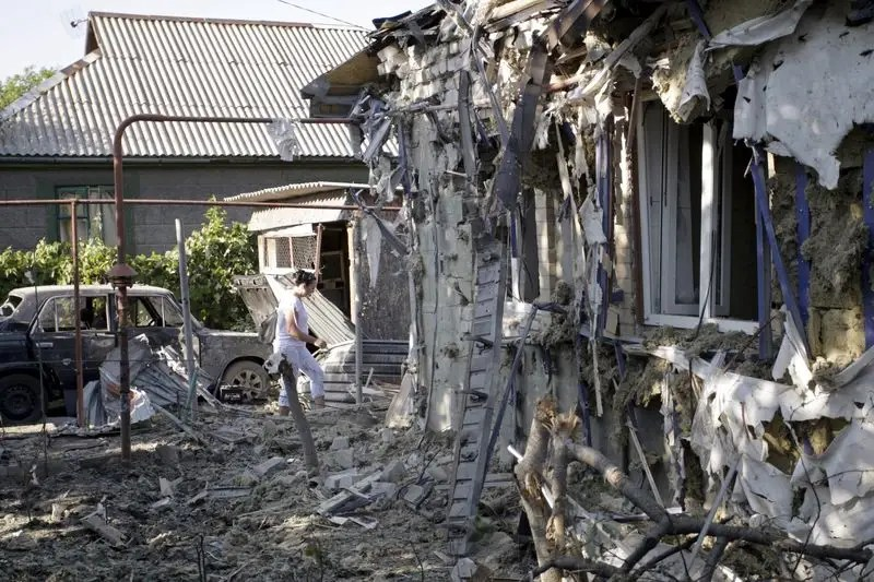 A woman walks near a residential building and a car, which locals said were damaged during recent shelling, in Donetsk, Ukraine, August 7, 2015. REUTERS/Alexander Ermochenko