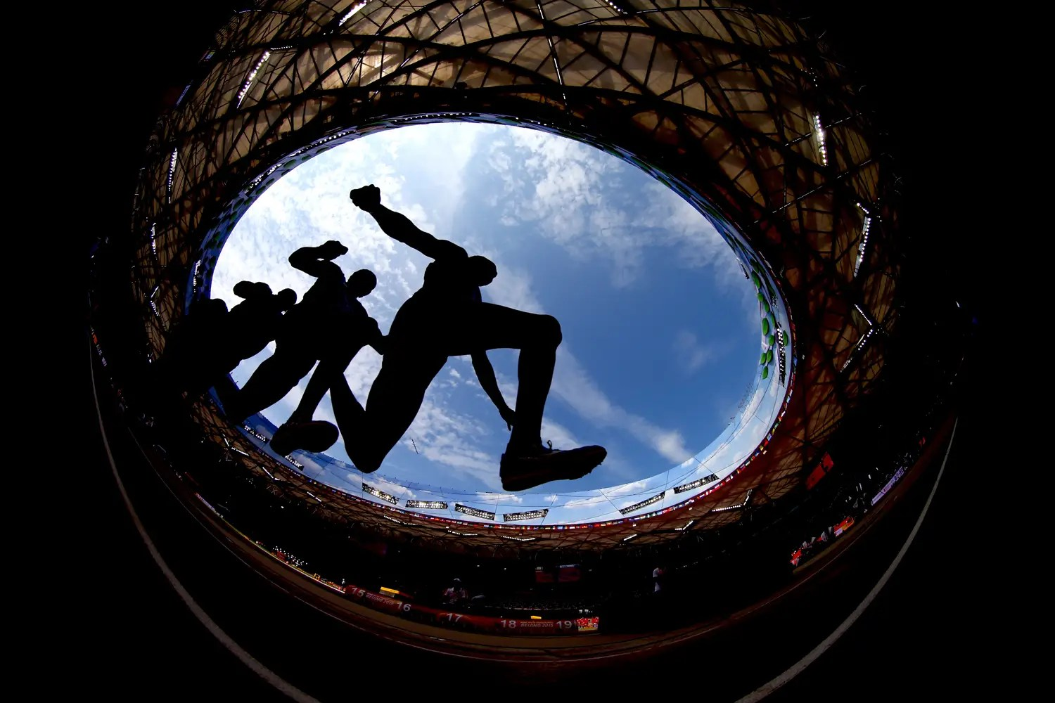 A triple-jumper takes off during qualification, with the Bird's Nest roof overhead.