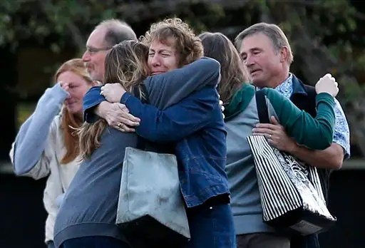 Faculty members embrace as they are allowed to return to Umpqua Community College Monday, Oct. 5, 2015, in Roseburg, Ore. The campus reopened to faculty for the first time since Oct. 1, when armed suspect Chris Harper-Mercer killed multiple people and wounded several others before taking his own life at Snyder Hall. (AP Photo/John Locher)