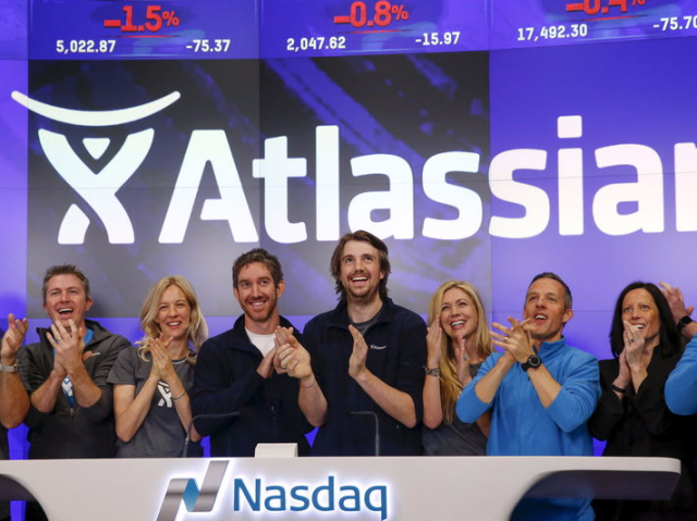 Mike Cannon-Brookes (C), co-founder and CEO of Atlassian Software Systems, and Scott Farquhar (3rd L), co-founder and CEO of Atlassian Software Systems, smile during it's opening PO at the Nasdaq at a MarketSite in New York, December 10, 2015. REUTERS/Shannon Stapleton