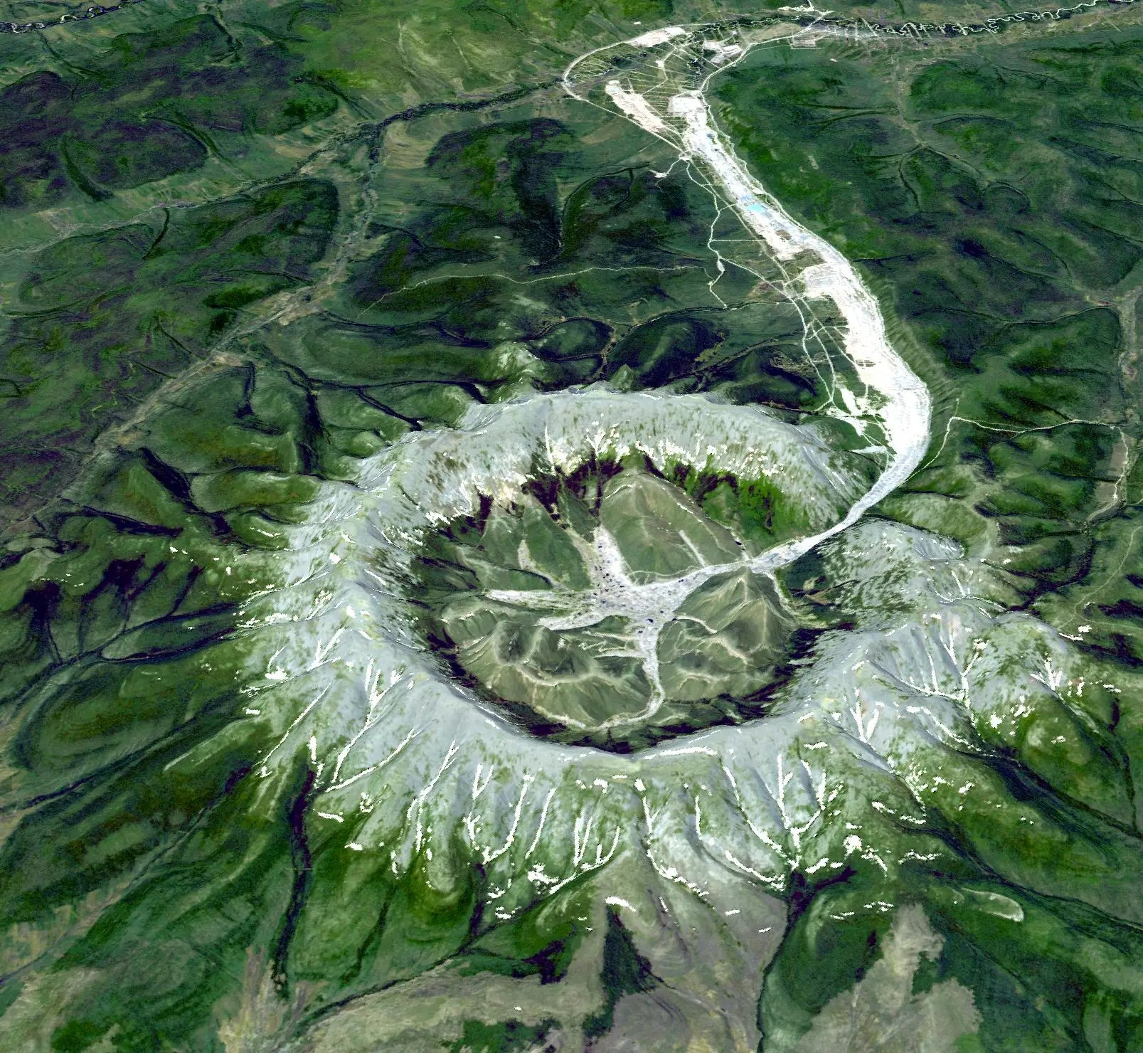 The perfectly circular intrusion of Kondyor Massif in Russia formed when molten magma crystallized underneath the earth and then rose to the surface. A stream flows out of its center.