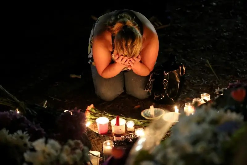 A woman mourns as she sits on the ground and takes part in a vigil for the Pulse night club victims following last week's shooting in Orlando, Florida. REUTERS/Carlo Allegri