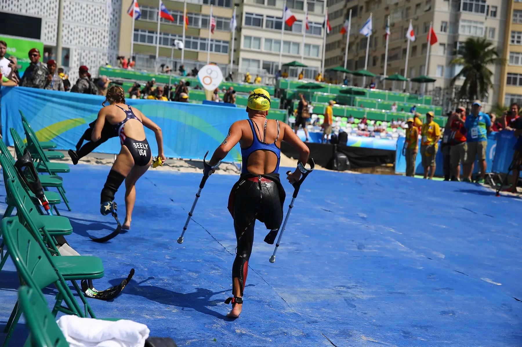 Los competidores corren por la playa en el triatlón de la mujer.