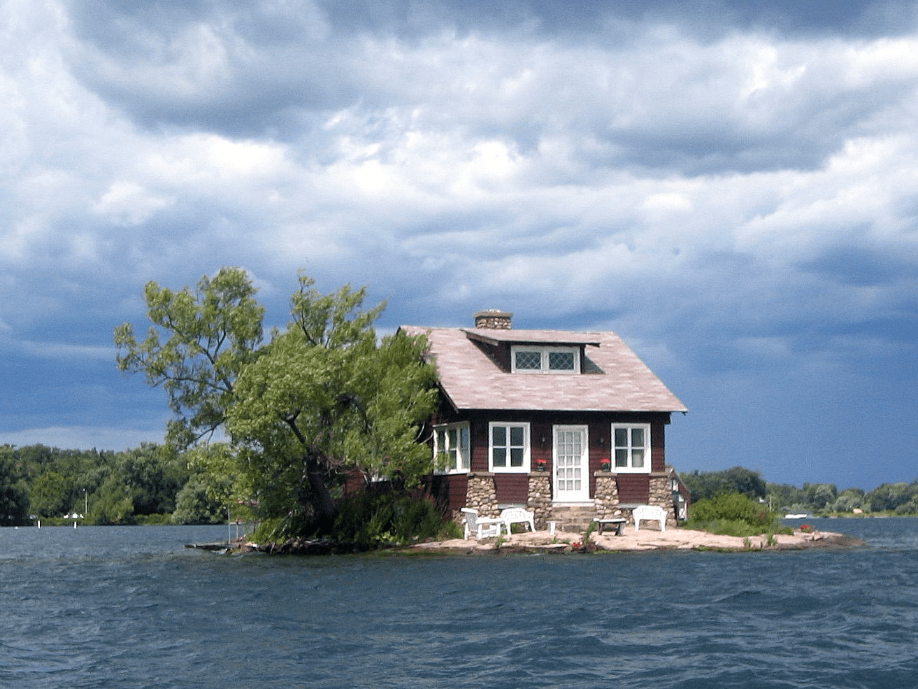 "Similarly, the island known as ""Just Room Enough Island"" is one of the famous Thousand Islands that straddle the US-Canada border in the Saint Lawrence River. There are a few lawn chairs out front on the family's tiny beach."