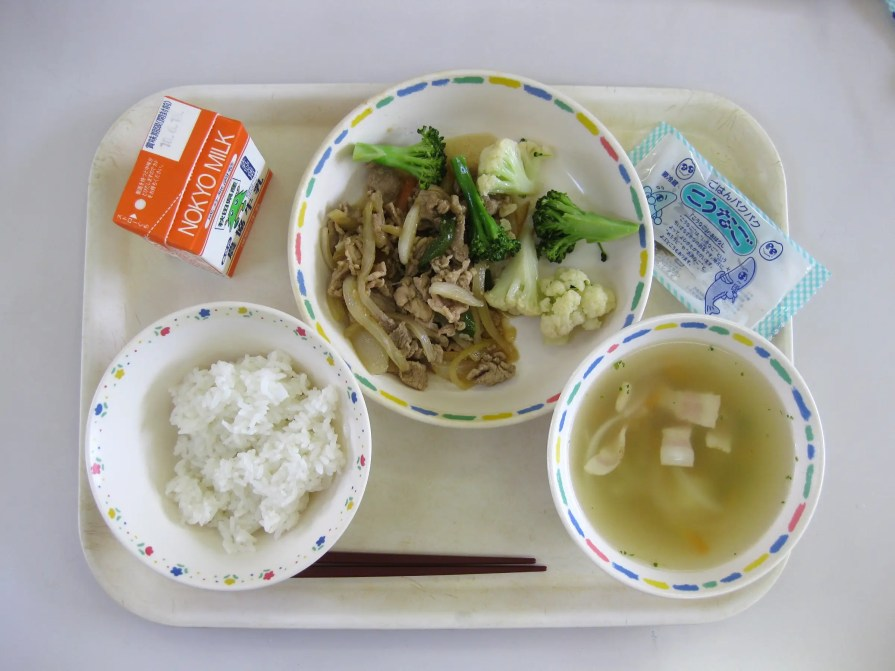Lunch often comes with a main dish, rice, and a side soup. This lunch has miso soup, a small packet of dried fish, milk, rice, and pork fried with vegetables.