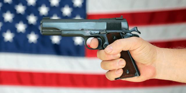 aiming gun american flag hand arms control regulation second amendment rights shutterstock_352729169