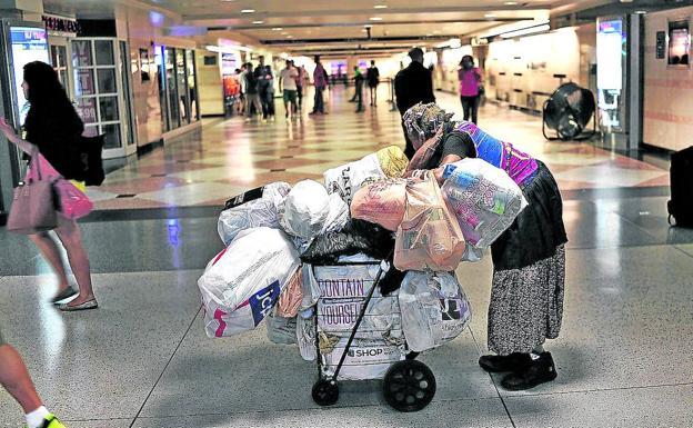 A homeless woman walks pushing a cart with her belongings through the corridors of a Manhattan station.