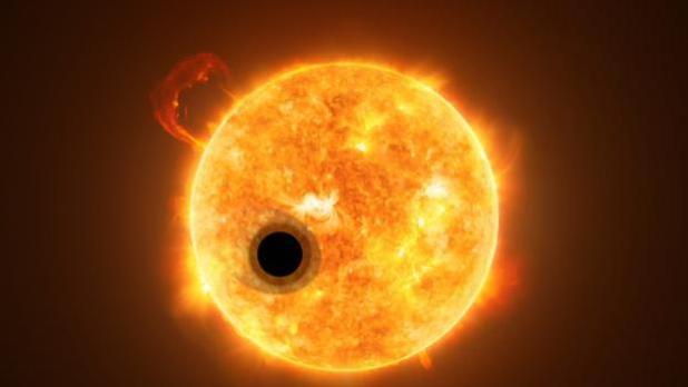 Interpretación artística del exoplaneta WASP-107b y su estrella, WASP-107. Parte de la luz de la estrella fluye a través de la capa de gas extendida del exoplaneta.