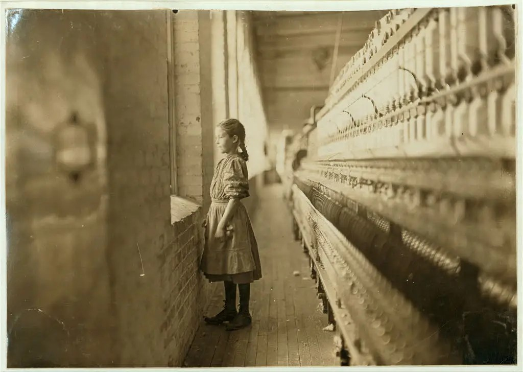 A spinner takes moment's glimpse of the outer world. She said she was 10 years old and had been working over a year. Lincolnton, North Carolina, November 1908.