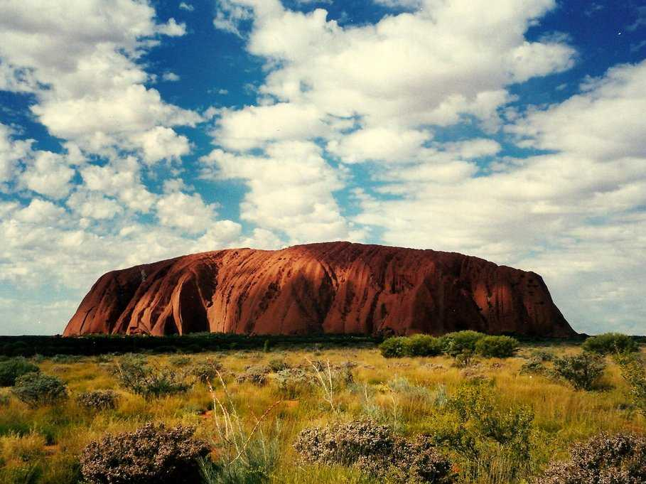 Witness a sunrise at Uluru, a massive sandstone rock formation in central Australia.