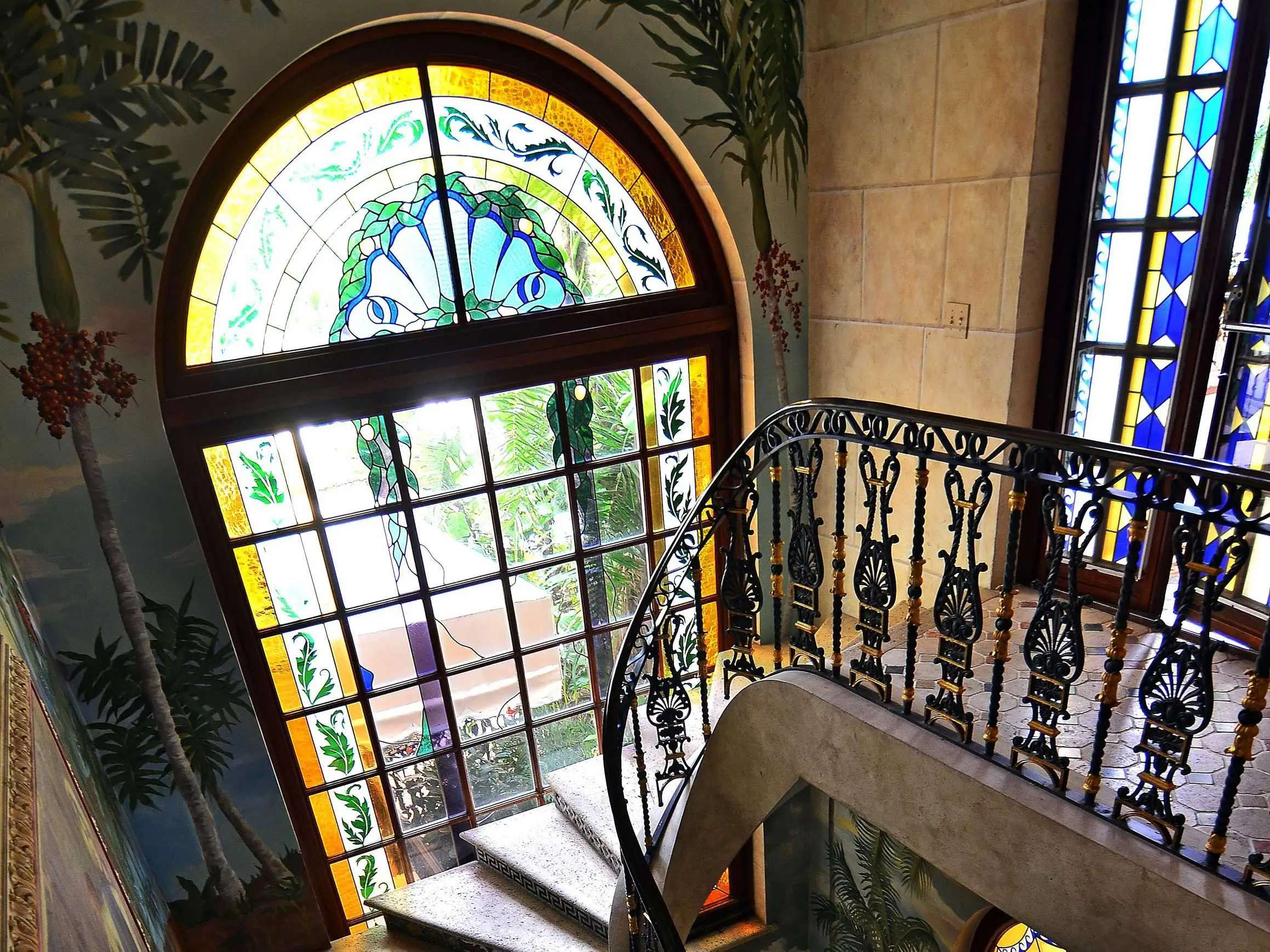There are plenty of opulent details throughout the home, like these stained glass windows, wall frescoes, and intricate staircase railing.