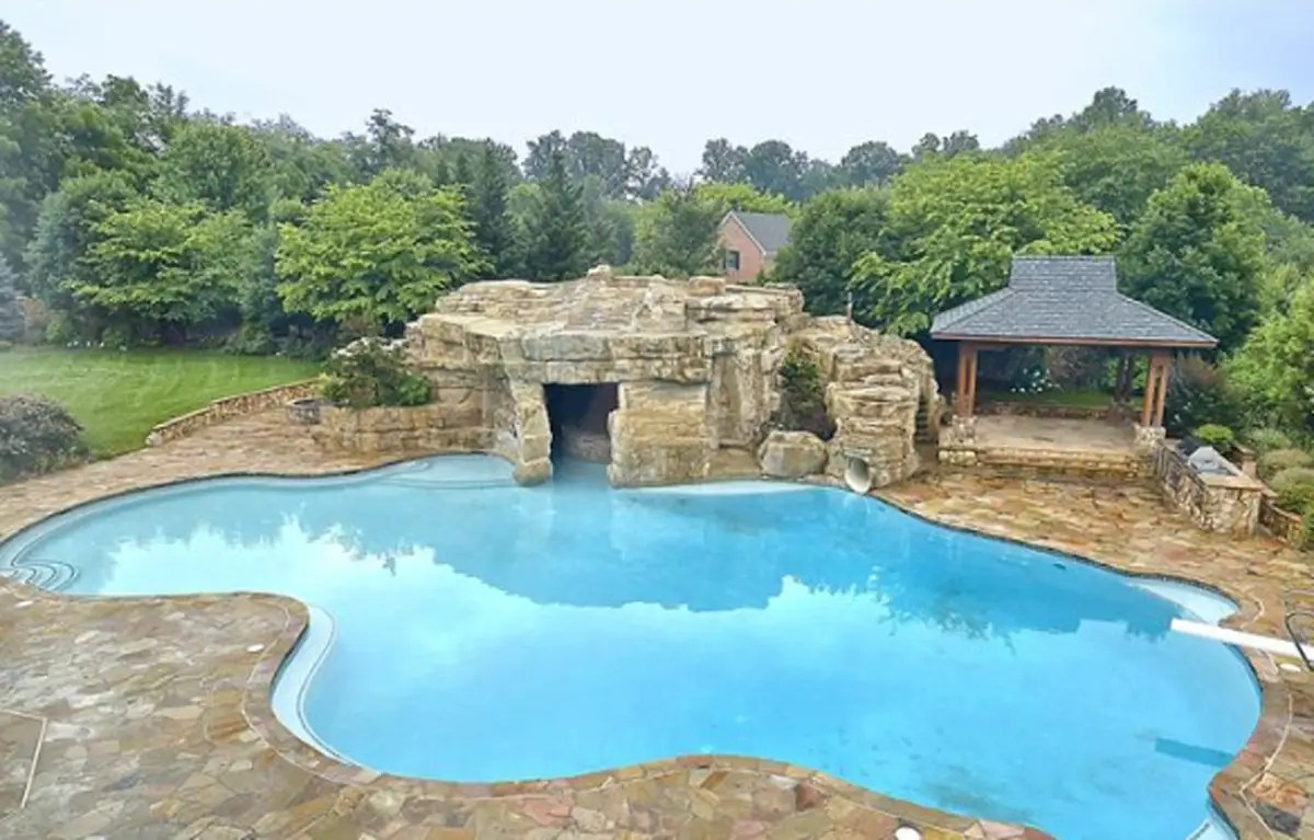 He has a fancy grotto next to his backyard pool complete with a bar, hot tub, and of course a water slide.