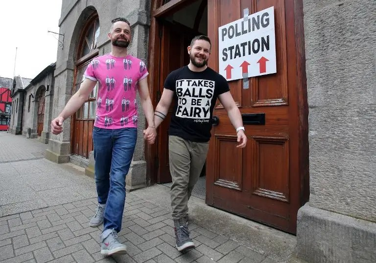 A couple pose holding hands as they walk out of a polling station after voting in Drogheda, north of Dublin on May 22, 2015