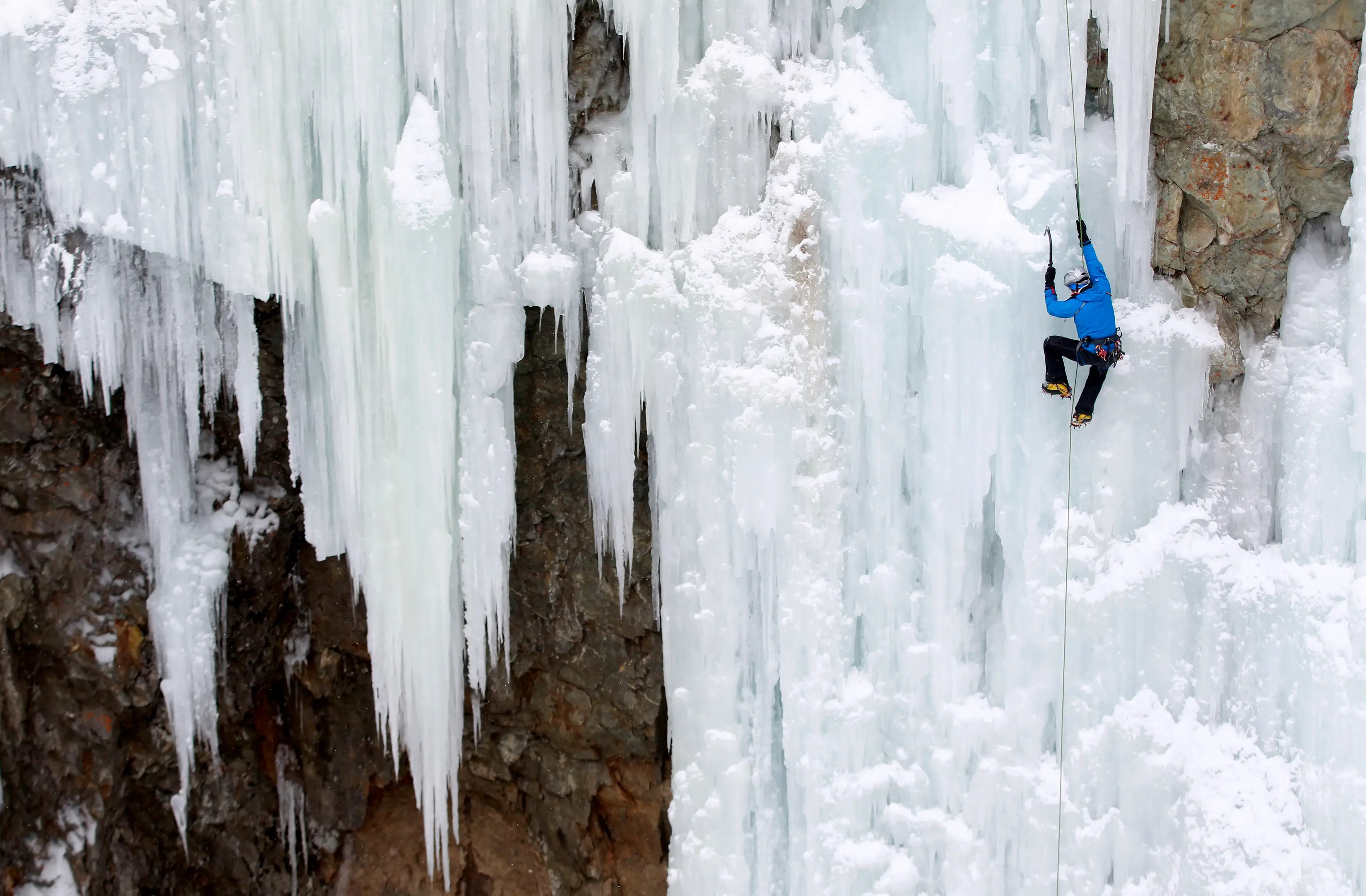 A man climbs up an artificially made wall of ice near the Swiss mountain resort of Pontresina.