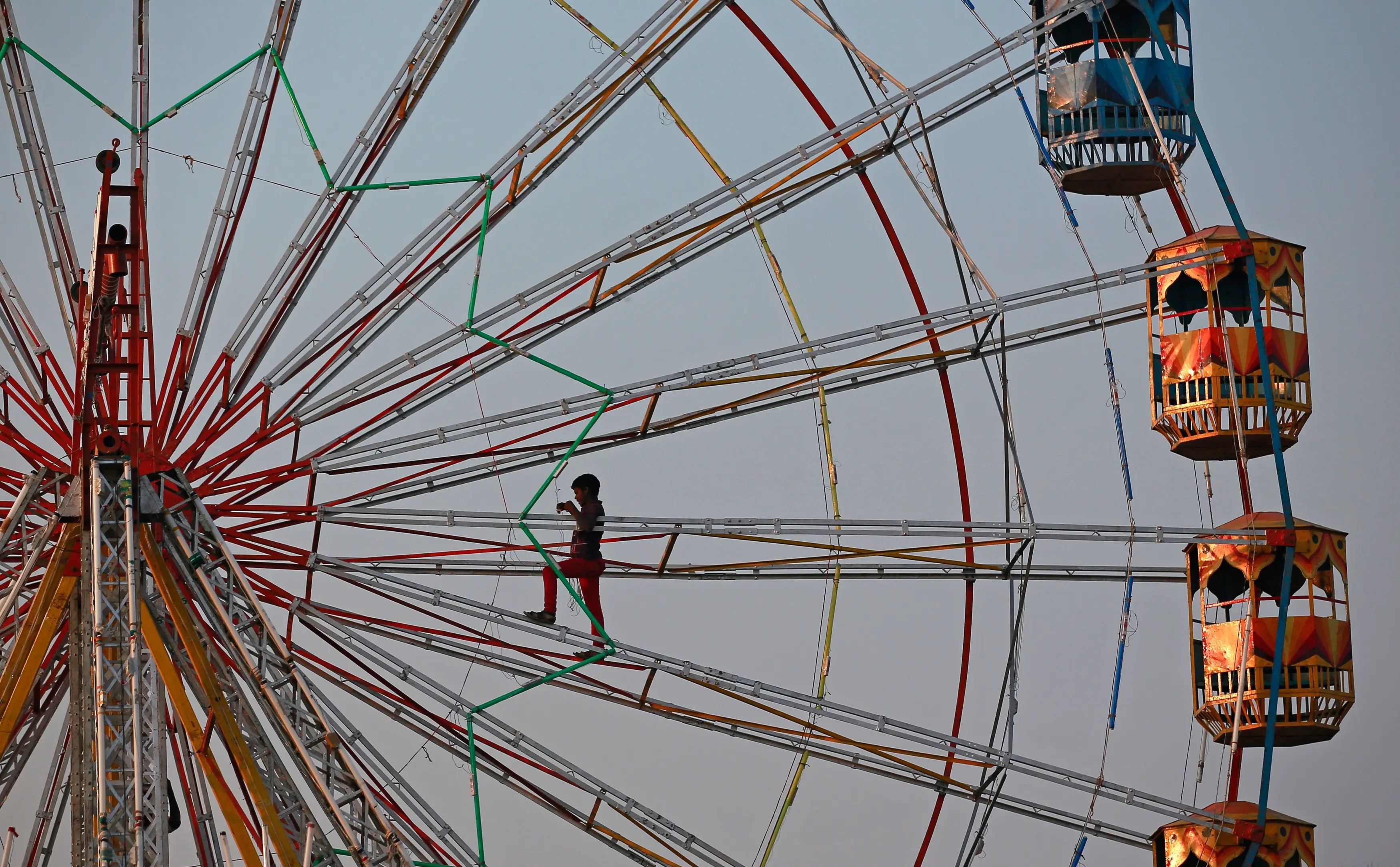 A worker installs lights while standing on a Ferris wheel at a fair in Mumbai.