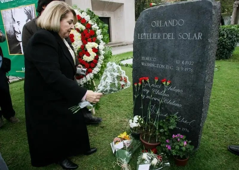 File photo of Isabel Morel, the widow of Orlando Letelier, a former Foreign Minister of Salvador Allende Government, who was killed when his car exploded 30 years ago in Washington in 1976, as she puts flowers on Letelier's grave in Santiago, September 21, 2006.  REUTERS/Victor Ruiz Caballero